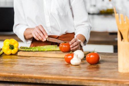 Photo pour Image recadrée de femme d'âge moyen coupant des légumes dans la cuisine - image libre de droit