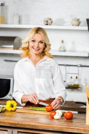 Photo pour Sourire attrayant femme d'âge moyen couper des légumes dans la cuisine et en regardant la caméra - image libre de droit