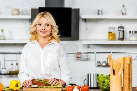 Photo pour Sourire belle femme d'âge moyen couper des légumes dans la cuisine et en regardant la caméra - image libre de droit