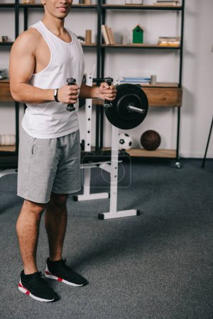 Photo for Cropped view of  bi-racial man workout with dumbbells in living room - Royalty Free Image