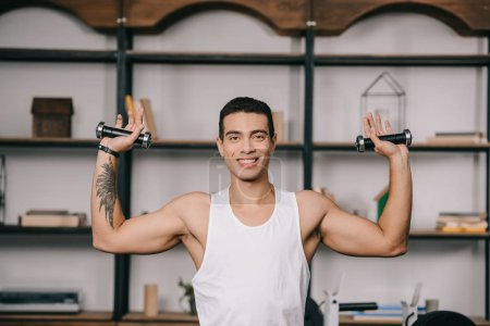 Photo for Tattooed  bi-racial man exercising with dumbbells - Royalty Free Image