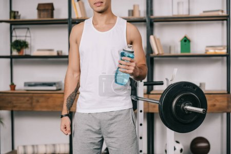 Photo for Cropped view of bi-racial man standing with sport bottle - Royalty Free Image