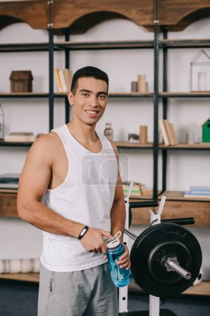 Photo for Cheerful  bi-racial man holding sport bottle and standing near barbell - Royalty Free Image