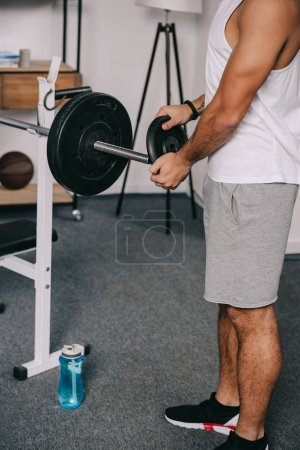 Photo for Cropped view of man putting heavy disk on barbell in living room - Royalty Free Image