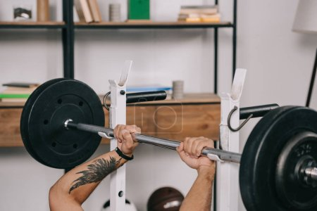 cropped view of man with tattoo workout with barbell in home gym