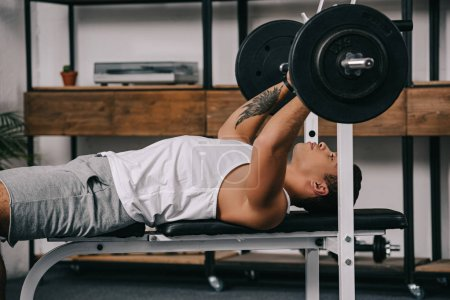 Photo for Tattooed mixed race man exercising with barbell in home gym - Royalty Free Image