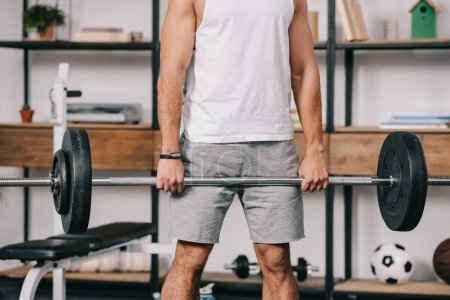 cropped view of muscular man exercising in home gym