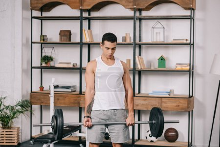 handsome tattooed bi-racial man exercising in home gym
