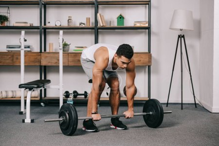 Photo for Handsome bi-racial man workout in home gym - Royalty Free Image