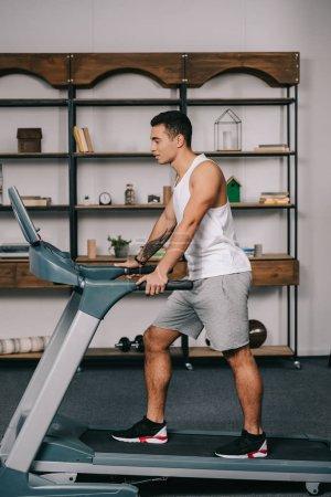 Photo for Muscular bi-racial sportsman walking on treadmill - Royalty Free Image