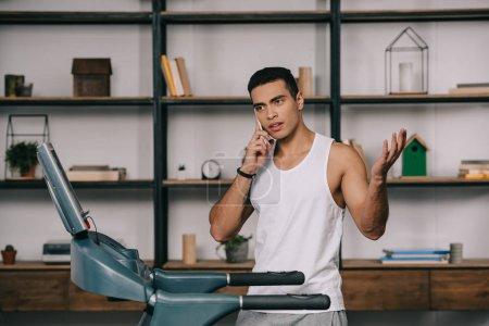 Photo for Bi-racial sportsman talking on smartphone near treadmill - Royalty Free Image