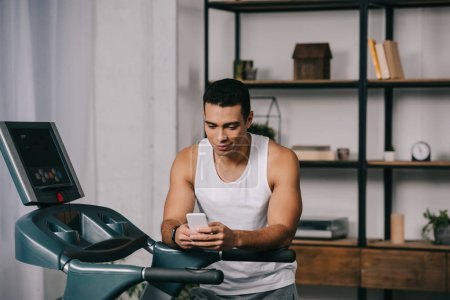 Photo for Muscular mixed race man using smartphone near treadmill - Royalty Free Image