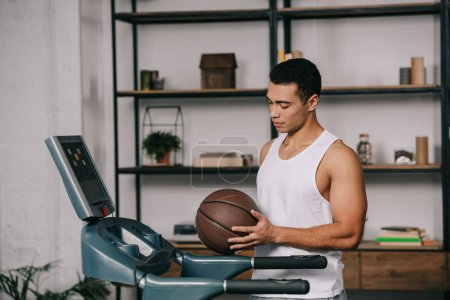 Photo for Handsome mixed race man holding basketball near treadmill - Royalty Free Image