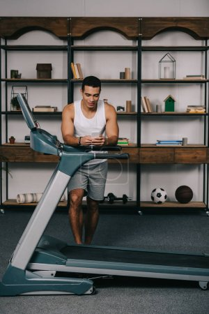 Photo for Strong mixed race man using smartphone near treadmill - Royalty Free Image