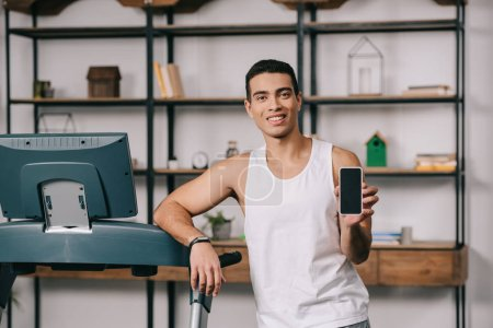 Photo for Handsome bi-racial man smiling and holding smartphone with blank screen - Royalty Free Image