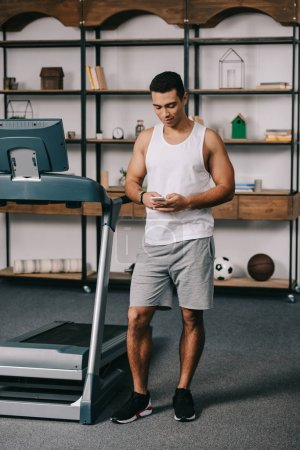 Photo for Full length of strong bi-racial man using smartphone near treadmill - Royalty Free Image