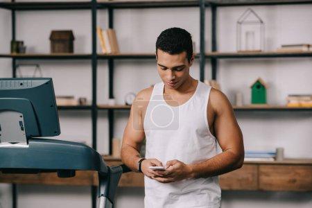 Photo pour Bel homme bi raciale fort à l'aide de smartphone dans le salon près de tapis roulant - image libre de droit