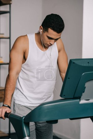 Photo for Mixed race man exercising on treadmill and listening music in earphones - Royalty Free Image