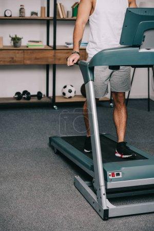 Photo pour Recadrée de l'homme, exercice sur tapis roulant dans le salon - image libre de droit