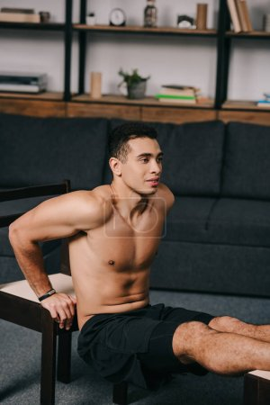 muscular bi-racial man exercising on chairs in living room