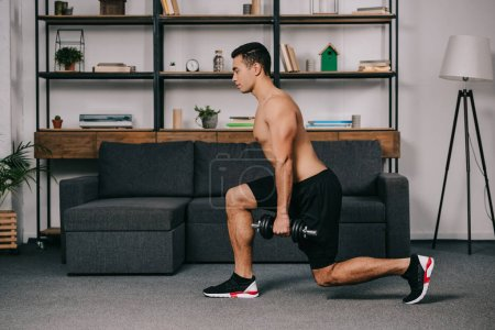 handsome mixed race man doing lunges exercise with heavy dumbbell in home gym