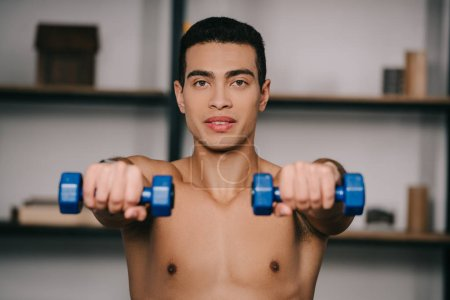 Photo for Selective focus of bi-racial man exercising with blue dumbbells - Royalty Free Image