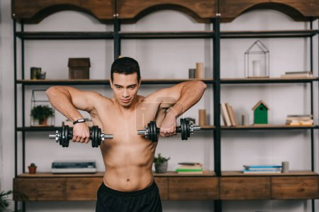 Photo for Strong bi-racial man exercising with heavy dumbbells - Royalty Free Image