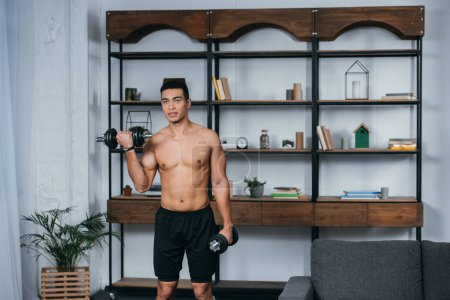 Photo for Strong bi-racial man workout with heavy dumbbells in living room - Royalty Free Image