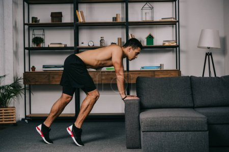Photo for Muscular mixed race man exercising near sofa in living room - Royalty Free Image