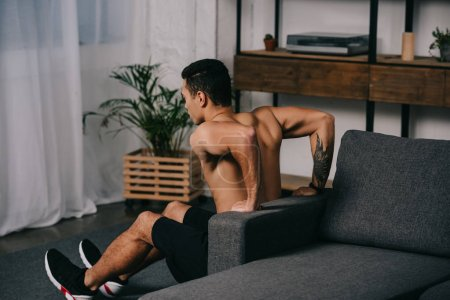 Photo for Tattooed mixed race man workout  near sofa in living room - Royalty Free Image