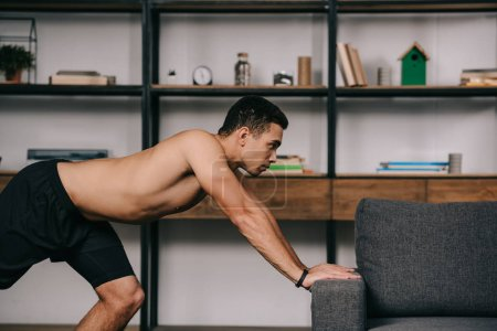strong mixed race man workout near sofa in living room