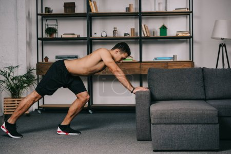 Photo for Handsome mixed race man doing exercise in living room - Royalty Free Image