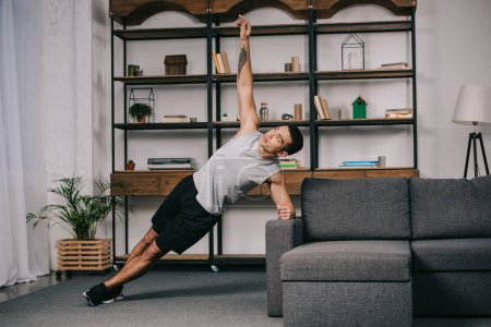 Foto de Hombre guapo de raza mixta con tatuaje haciendo ejercicio de plank cerca de sofá en la sala de estar - Imagen libre de derechos