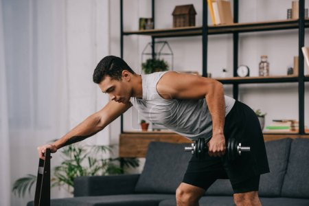 Photo for Handsome bi-racial man holding chair and doing exercise with dumbbell - Royalty Free Image
