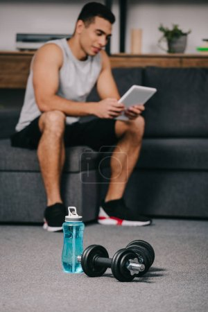 Photo for Selective focus of sport bottle near dumbbells with bi-racial man holding digital tablet on background - Royalty Free Image