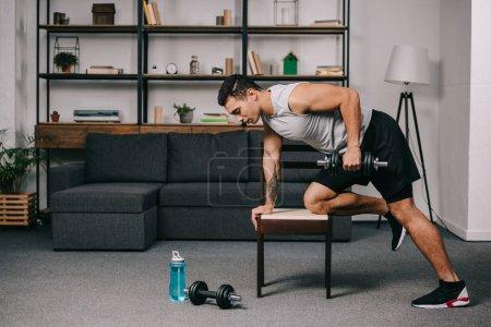 Photo pour Homme bi raciale fort, faire des exercices avec haltères sur chaise dans la salle de séjour - image libre de droit