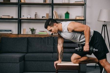 Photo for Tattooed bi-racial man doing exercise with dumbbell on chair in living room - Royalty Free Image
