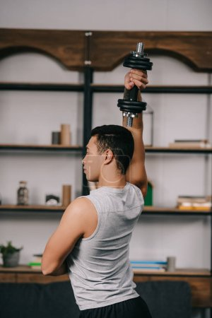 strong bi-racial man exercising with dumbbell in living room