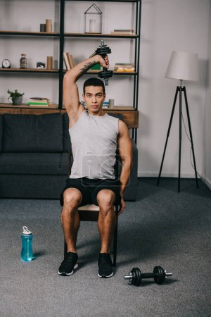 Photo for Strong tattooed bi-racial man workout with dumbbell on chair in living room - Royalty Free Image