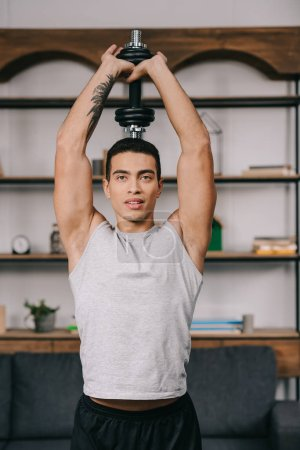 Photo for Handsome bi-racial man standing in sportswear and holding dumbbell over head - Royalty Free Image