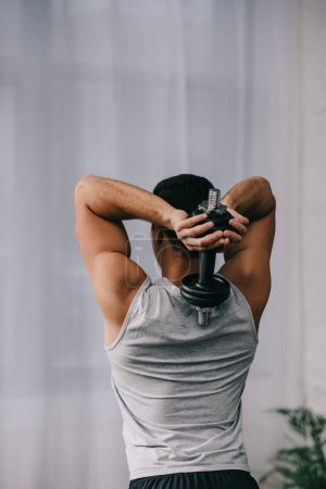 Photo for Back view of man standing in sportswear and holding dumbbell - Royalty Free Image