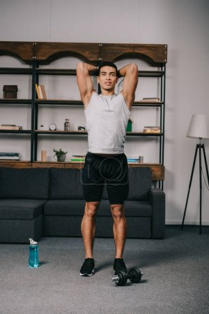 bi-racial man standing in sportswear and workout in living room