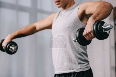 Photo for Cropped view bi-racial man workout with dumbbells - Royalty Free Image