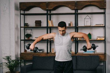 Foto de Hombre bi racial hacer ejercicio con pesas en la ropa de deporte en sala de estar - Imagen libre de derechos