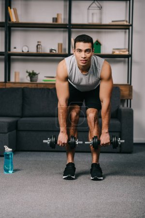 Photo for Handsome mixed race man workout with dumbbells near sport bottle - Royalty Free Image