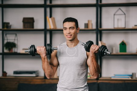 Photo for Smiling mixed race man workout with dumbbells in living room - Royalty Free Image