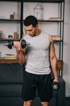 Photo for Handsome mixed race man looking at muscles while exercising - Royalty Free Image