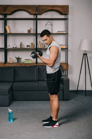 Photo for Handsome mixed race man looking at muscles while doing exercise in living room - Royalty Free Image