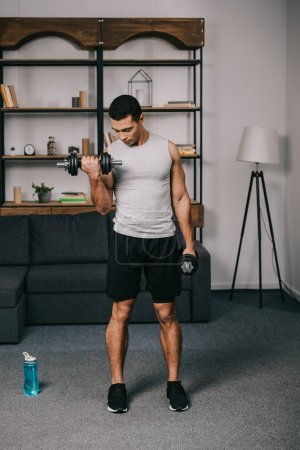 Photo for Mixed race man looking at muscles on hand while doing exercise in living room - Royalty Free Image