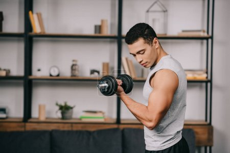 Photo for Handsome mixed race man looking at muscles on hand while doing exercise with dumbbell in living room - Royalty Free Image